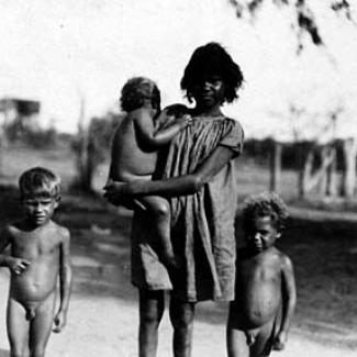 A black and white photograph of an adult and young children at Roper River Mission. The adult is holding one child, while the other two children are walking.