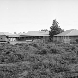 A black and white photograph of several buildings at Umeewarra Mission Children's Home. A chain link fence surroundings the buildings, while beyond the fence is a grassy plain.