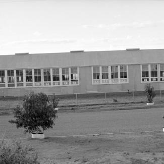 A black and white photograph of a building at Umeewarra Mission Children's Home. The building is separated from the road by a chain link fence. The building itself is long, with most of its length covered by window. Inside the windows hang cards that spell: Umeewarra School.