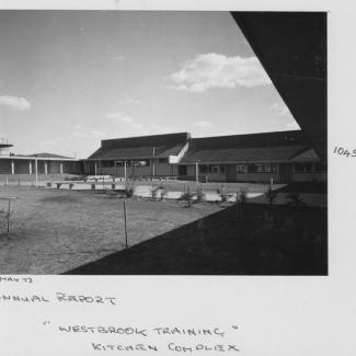 A black and white photograph of Westbrook Training Centre. On the photograph is written: May seventythree, Annual Report, Westbrook Training, Kitchen Complex. The kitchen building opens out into a large grassy space with several saplings.