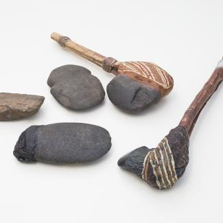 Two ancient tools comprised of a painted stone head afixed to a wooden handle rest alongside three stone axe-head artefacts.