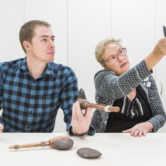 A man holds an ancient stone hatchet while the woman next to him examines a stone axe-head. More examples of ancient tools rest on the table infront of them.