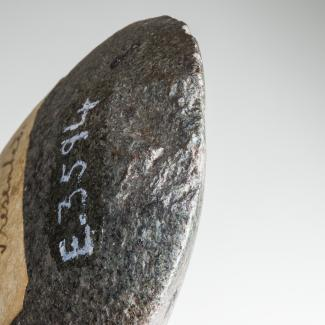 A close-up photograph of an ancient stone axe-head, lightly chipped at the edge and labelled in white paint with a cataloging number.